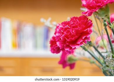 beautiful carnations inside a room with books