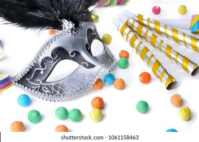 beautiful carnival mask among colorful cotillons on white white backgroung
