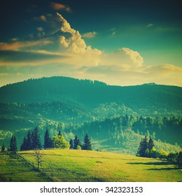 Beautiful Carpathian mountain valley with colorful clouds in a sunset light. Vintage colors