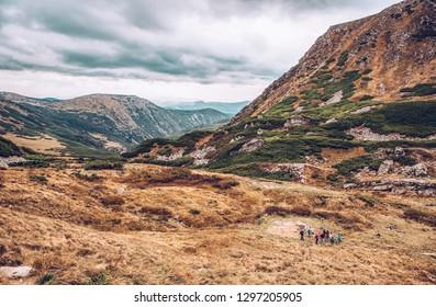 Beautiful Carpathian mountains in autumn season.Travel destination for active tourism in Europe.Vintage film filter.Group of tourist enjoy nature beauty
