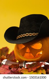 beautiful carved halloween pumpkin in hat and with a knife on a yellow  background