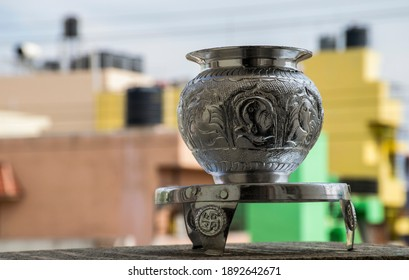 Beautiful carved silver pot or kalash and stand used in hindu rituals, on blur background.