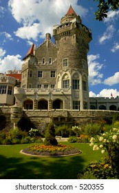 A beautiful castle and it's lush green garden, set against a blue sky with white fluffy clouds