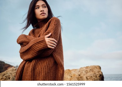 Beautiful casual Asian girl in cozy knitted sweater dreamily looking away by the sea