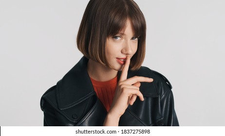 Beautiful casual brunette girl with bob hair has intriguing look asking to keep secret isolated on white background. Shh expression