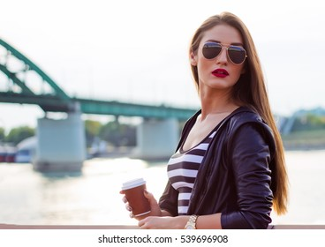 Beautiful casual business woman, girl with coffee at river sunset.
