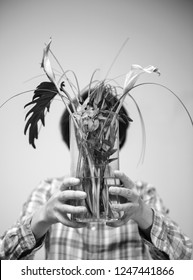 Beautiful casual dressed woman hiding her face behind flower vase with two dead cala flower and multiple green leaves deadpan style vertical black and white