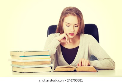 Beautiful casual student woman sitting by stack of books.