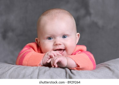 Beautiful Caucasian Baby Girl with Blue Eyes and hands at her mouth