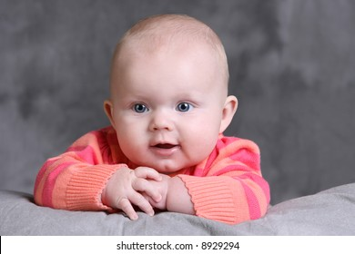 Beautiful Caucasian Baby Girl with Blue Eyes and hands near her face
