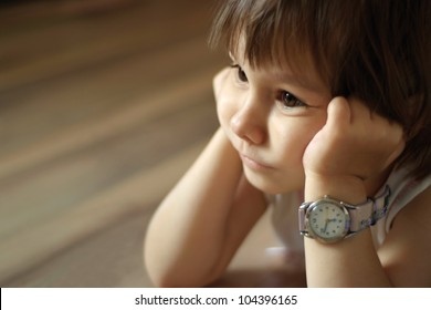 A beautiful Caucasian baby lies with the clock on a light background