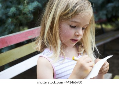 Beautiful Caucasian blond girl sitting on old park bench drawing picture