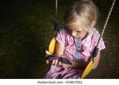 Beautiful Caucasian blond girl sitting on swing watching and playing on smart phone.