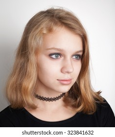 Beautiful Caucasian blond teenage girl in black choker necklace. Studio portrait over white background with soft shadow