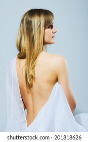 Beautiful caucasian blond young woman is wearing white cloth with naked back and shoulder on light background