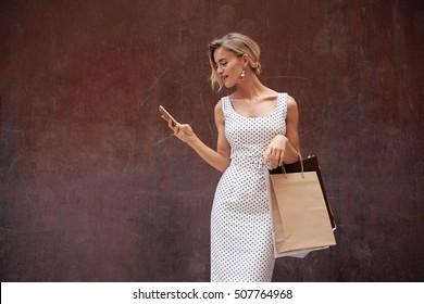 Beautiful caucasian blonde female wearing white summer dress with black polka dots is looking at the screen of the mobile phone while standing on a dark brown background with a blank paper bags.