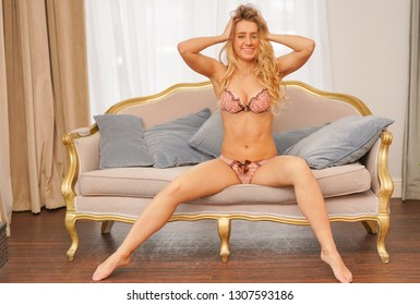beautiful caucasian blonde girl in pink lace lingerie on the couch with pillows on the background of the window with curtains