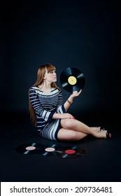 Beautiful caucasian blonde girl wearing striped dress with vinyl discs