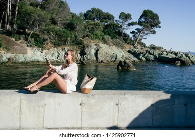 Beautiful caucasian blonde woman enjoy the beautiful seascape of l'esterel region posing glamourously on a rocks and using her smartphone