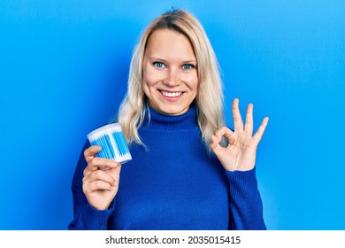 Beautiful caucasian blonde woman holding earwax cotton remover doing ok sign with fingers, smiling friendly gesturing excellent symbol