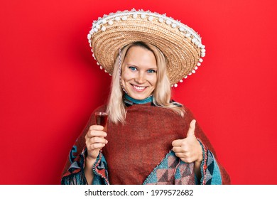 Beautiful caucasian blonde woman wearing festive mexican poncho drinking tequila shot smiling happy and positive, thumb up doing excellent and approval sign