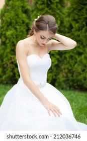 Beautiful, caucasian, blue eyes woman wearing a wedding dress with natural background