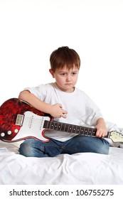 Beautiful Caucasian boy plays the guitar