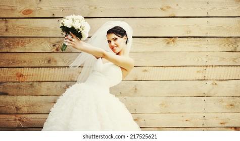 Beautiful caucasian brunette bride on wooden background.