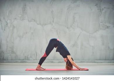 Beautiful Caucasian brunette doing Downward-Facing Dog yoga pose on mat barefoot.