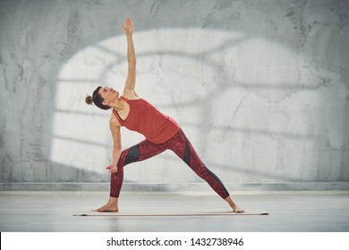 Beautiful Caucasian brunette doing Revolved Warrior with Arms Extendedyoga pose on mat barefoot.