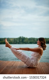 Beautiful caucasian brunette dressed in white sitting in Boat yoga pose on pier.