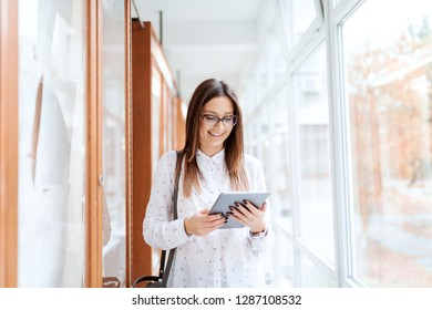 Beautiful Caucasian brunette standing next to noticeboard and using tablet while standing in university building.