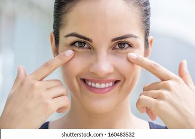 Beautiful caucasian brunette young woman touching the skin under her eye.