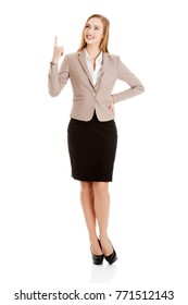 Beautiful caucasian business woman is pointing up.