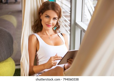 Beautiful caucasian business woman sitting in her modern office relaxation zone in casual outfit. Woman smiles friendly, reading, working using tablet. She is in hammock, on fake grass