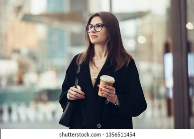 Beautiful caucasian businesswoman walking to the office on city street with coffee cup wearing eyeglasses