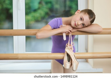 Beautiful caucasian child at ballet studio. Little tired ballerina after ballet dance classes. Studio of ballet arts.