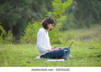 beautiful caucasian college student with laptop working outdoor with beautiful light and nature background, beautiful caucasian texting on laptop