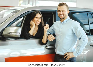 beautiful caucasian couple purchased new car in dealership, posing in car showroom. happy owners of new automobile
