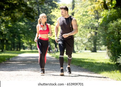 Beautiful caucasian couple running together outdoor at sunny day.