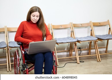 Beautiful Caucasian disabled woman sitting wheel chair and work with laptop indoor