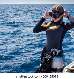 Beautiful, Caucasian diver on a boat in the ocean putting on goggles in preparation for scuba diving.