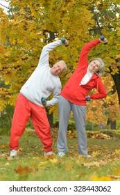 Beautiful caucasian elderly couple trainig in the park in autumn