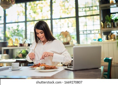 Beautiful caucasian elegant brunette sitting in restaurant and eating sausage for breakfast. On table is laptop.