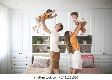 Beautiful Caucasian family with two children, dad and mom hold in their arms in the air two sisters toddlers, a child with Down syndrome in the family, a real interior