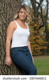 Beautiful Caucasian female model poses in white tank top and blue jeans in park leaning against tree and smiling as looks down and right