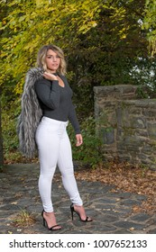 Beautiful Caucasian female model poses holding a faux fur vest and white pants in park in autumn