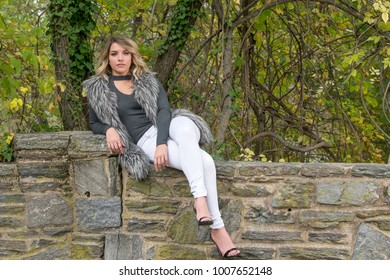 Beautiful Caucasian female model poses wearing a faux fur vest and white pants in park in autumn - sitting on stone wall