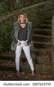 Beautiful Caucasian female model poses wearing a faux fur vest and white pants stands in outdoors stairs in autumn