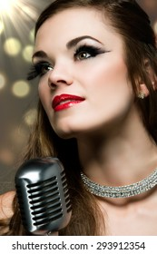 Beautiful caucasian female singer. The girl is holding a retro performance microphone and wearing a black evening dress with a diamond choker necklace and glamor make-up.
